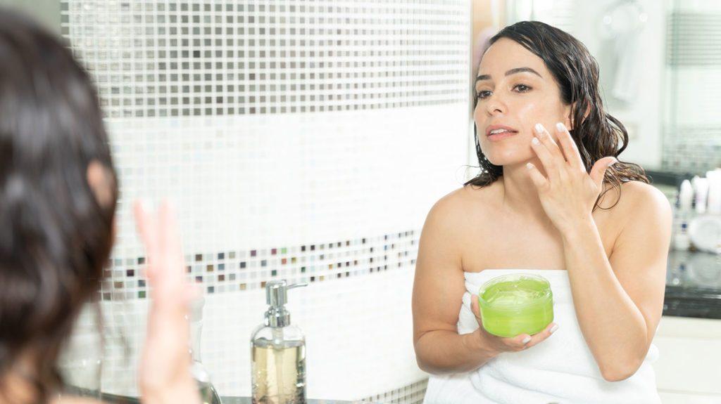 Una mujer se aplica gel de aloe vera en el rostro después de la ducha para usarlo como tónico facial.